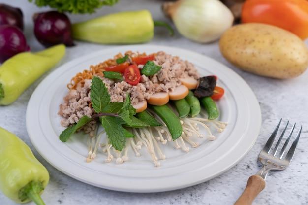 Fideos salteados con carne picada de cerdo, edamame, tomates y champiñones en un plato blanco.