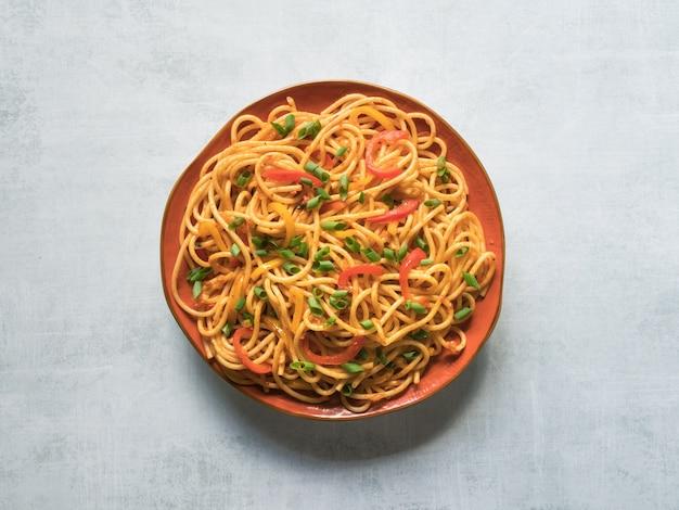 Fideos schezwan con verduras en un plato. vista superior.