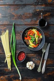Fideos soba con ternera, zanahorias, cebollas y pimientos dulces. vista superior.