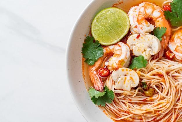 Fideos con sopa picante y camarones en un tazón blanco (tom yum kung) - estilo de comida asiática