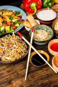 Fideos tailandeses; ensalada; rollitos de primavera; arroz; brotes de alubias; salsas con palillos en mesa de madera.