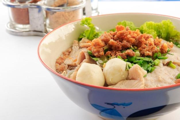 Fideos tailandeses con máquina de cerdo y albóndigas y verduras frescas y sopa caliente sazonador