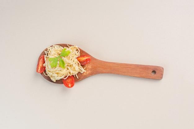 Fideos y tomates en rodajas en una cuchara, sobre el mármol.