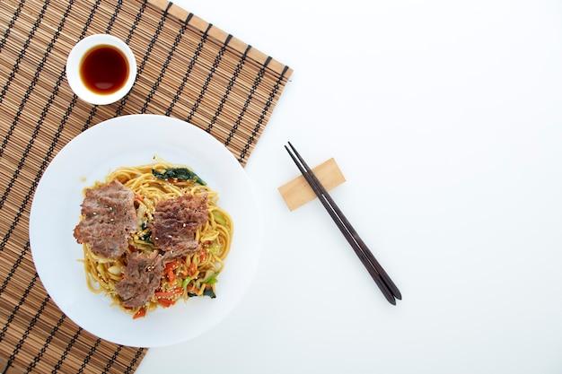 Fideos udon con verduras, carne de res.