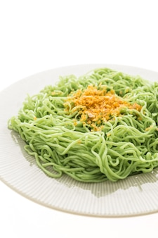 Fideos verdes o de jade en plato blanco.
