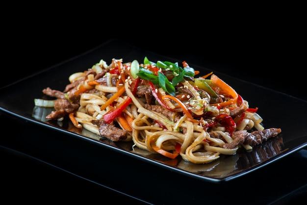 Fideos con verduras con carne de cerdo, pollo, pescado, vieira, carne de res, camarones en un plato negro sobre una pared negra.
