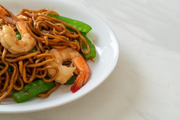 Fideos yakisoba salteados con guisantes y camarones - estilo de comida asiática