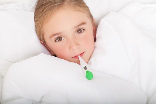 Fiebre, resfriado y gripe: medicamentos y té caliente en una niña enferma en la cama