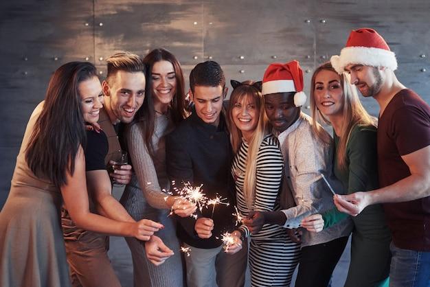 Fiesta con amigos. grupo de jóvenes alegres llevando bengalas y flautas de champán