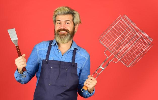 Fiesta de barbacoa. concepto culinario. fin de semana de verano. feliz hipster mantenga utensilios de cocina para barbacoa. chef hombre barbudo. herramientas para asar carne al aire libre. picnic y barbacoa. listo para fiesta de barbacoa.