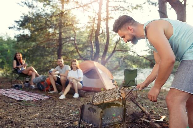 Fiesta, campamento de grupo de hombres y mujeres en el bosque. se relajan, cantan una canción y cocinan barbacoa contra la hierba verde. las vacaciones, verano, aventura, estilo de vida, concepto de picnic.