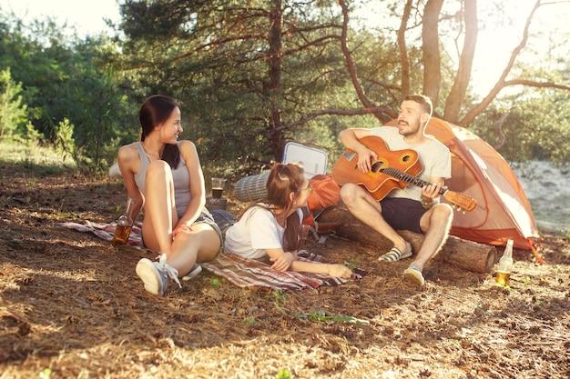 Fiesta, campamento de grupo de hombres y mujeres en el bosque. se relajan, cantan una canción contra la hierba verde. las vacaciones, verano, aventura, estilo de vida, concepto de picnic.