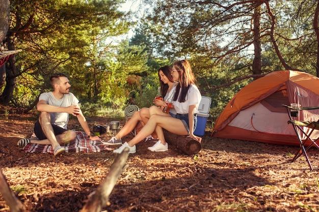 Fiesta, campamento de grupo de hombres y mujeres en el bosque. se relajan contra la hierba verde. concepto