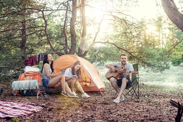 Fiesta, campamento de grupo de hombres y mujeres en el bosque. relajante, cantando una canción contra la hierba verde.