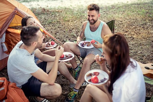 Fiesta, campamento de grupo de hombres y mujeres en el bosque. relajarse y comer barbacoa contra la hierba verde. vacaciones, verano, aventura, estilo de vida, concepto de picnic