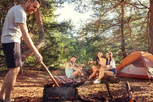 Fiesta, campamento de grupo de hombres y mujeres en el bosque. vacaciones, verano, aventura, estilo de vida, concepto de picnic