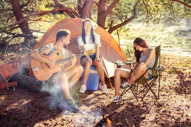 Fiesta, campamento de grupo de hombres y mujeres en el bosque.