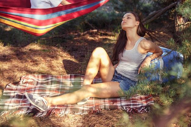 Fiesta, campamento de hombres y mujeres en el bosque. se relajan y comen barbacoa