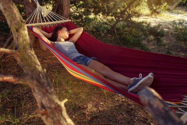 Fiesta, camping. mujer durmiendo en el bosque. ella relajante