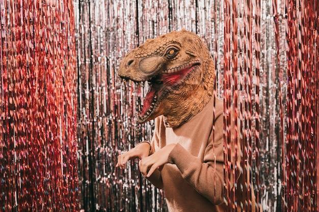 Fiesta de carnaval de alto ángulo con disfraz de dinosaurio