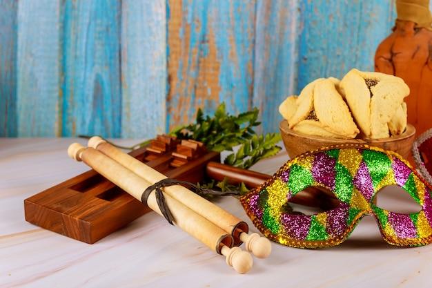 Fiesta de carnaval judío tradicional celebración de purim y galletas hamantaschen, matraz y máscara
