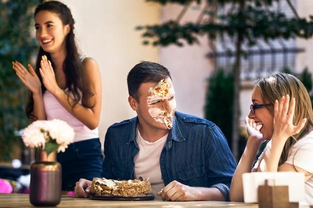 Fiesta de celebración para un cumpleaños de un niño adulto con un pastel y una broma en la cara