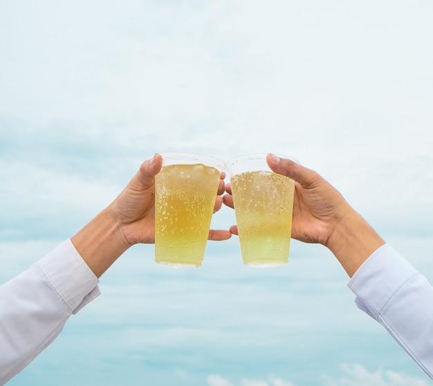 Fiesta de celebración, las manos sostienen cervezas de bebidas con vasos de plástico y animan al éxito con un hermoso cielo como fondo