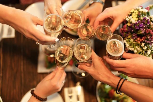 Fiesta de chicas. niñas aclama gafas con champán en el restaurante.