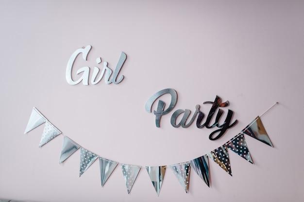 Fiesta de chicas de texto. guirnalda de banderas de papel plateado sobre fondo rosa. decoración de fiesta de cumpleaños, vista superior, espacio de copia.