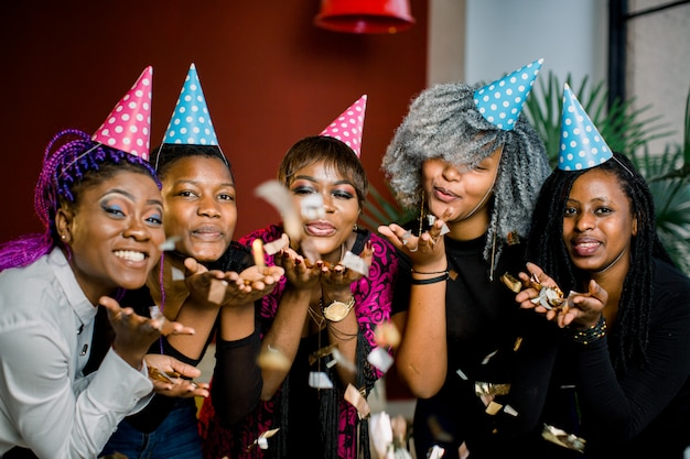 Fiesta de confeti feliz joven grupo africano de personas celebrando la víspera de año nuevo y soplando confeti