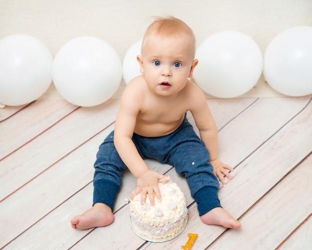 Fiesta de cumpleaños de un año bebé. bebé comiendo y aplastando pastel de cumpleaños