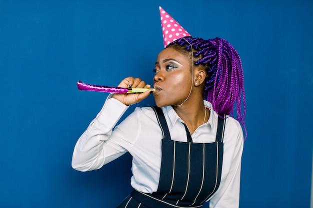 Fiesta de cumpleaños, carnaval de año nuevo. joven africana sonriente en el espacio azul celebrando evento brillante, viste elegante falda blanca de moda y pantalón negro, con sombrero de fiesta rosa con matraca.