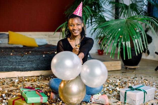Fiesta de cumpleaños, carnaval de año nuevo. mujer sonriente africana joven que celebra evento brillante ,. confeti chispeante, divertirse, bailar y beber champán