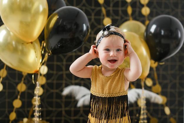 Fiesta de cumpleaños de niña bebé decorada con globo negro y dorado.