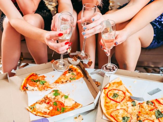 Fiesta de cumpleaños. toma recortada de chicas celebrando un evento especial, sentadas frente a una pizza, sosteniendo copas con champán.