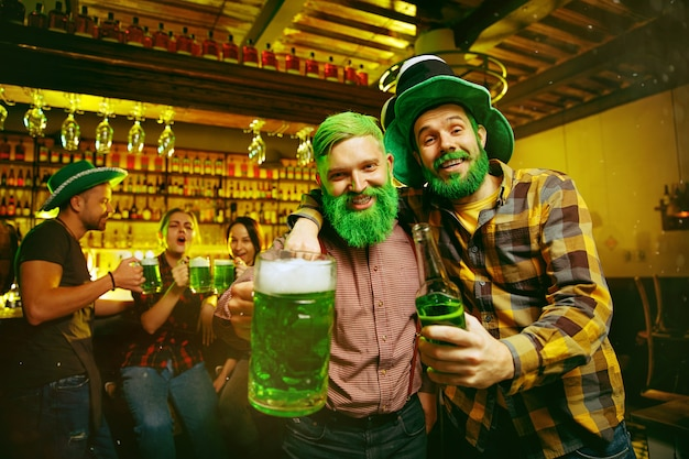 Fiesta del día de san patricio. amigos felices está celebrando y bebiendo cerveza verde. hombres y mujeres jóvenes con sombreros verdes. interior del pub.