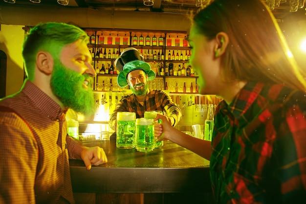 Fiesta del día de san patricio. amigos felices están celebrando y bebiendo cerveza verde. hombres y mujeres jóvenes con sombreros verdes. interior del pub.
