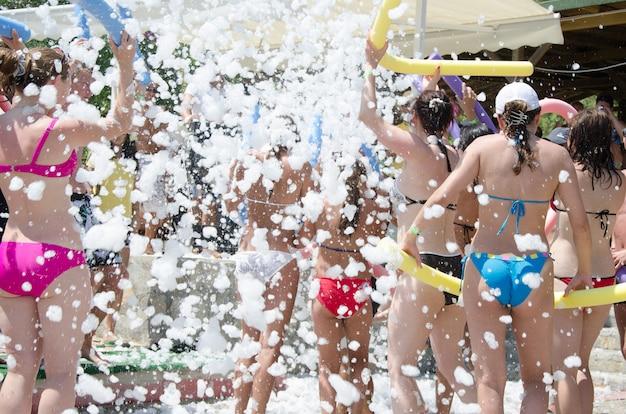 Fiesta de espuma en la playa. la gente baila música con espuma
