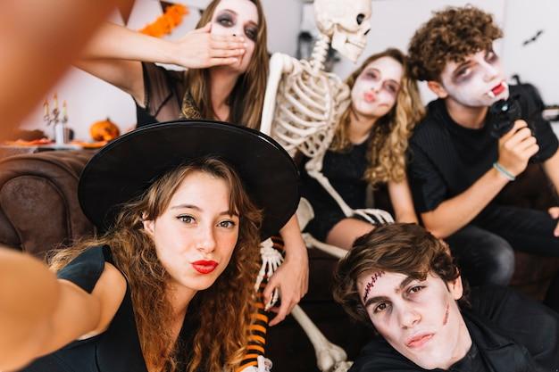 Fiesta de halloween con adolescentes haciendo besos de aire