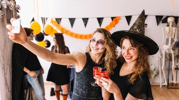 Fiesta de halloween con bruja y zombie haciendo selfie