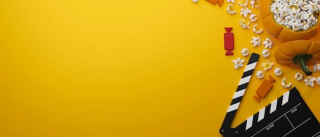 Fiesta de halloween caramelos palomitas de maíz cubo película badajo copia espacio para texto en fondo amarillo