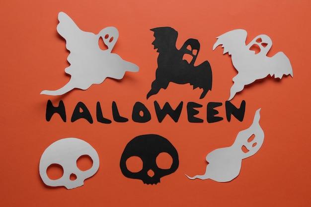 Fiesta de halloween. composición con diferentes figuras de papel de halloween. vista desde arriba. sobre fondo naranja