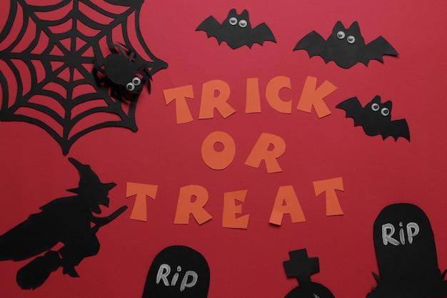 Fiesta de halloween. composición con varias figuras de papel de halloween. vista desde arriba. sobre fondo rojo