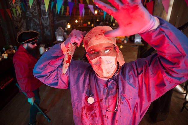 Fiesta de halloween con hombres disfrazados de monstruos aterradores. doctor espeluznante. pirata aterrador en el fondo.