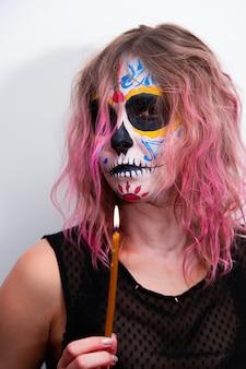 Fiesta de halloween, retrato de una niña con maquillaje sosteniendo una vela en la mano.