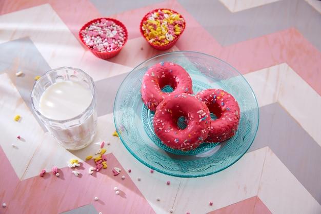 Fiesta infantil con donas rosa leche y aderezos de cupcake.