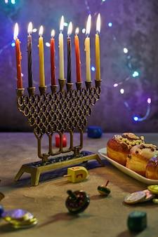 Fiesta judía de janucá. un plato tradicional son las rosquillas dulces. mesa de hanukkah colocando un candelabro con velas y trompos