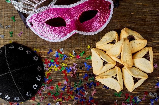 Fiesta judía de purim con máscara de carnaval y galletas hamantaschen. lay flat