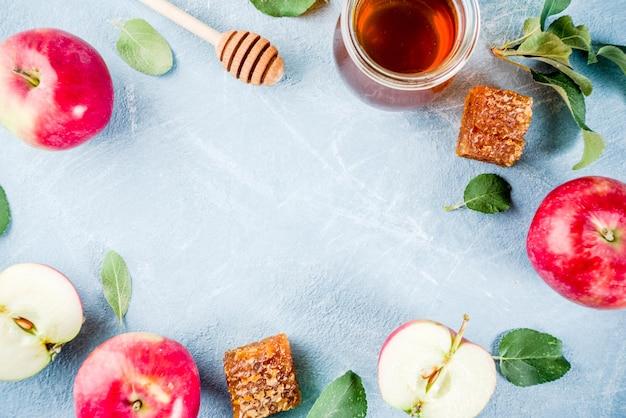 Fiesta judía de rosh hashaná o concepto de día de fiesta de manzana, con manzanas rojas, hojas de manzana y miel en frasco, marco de fondo azul claro