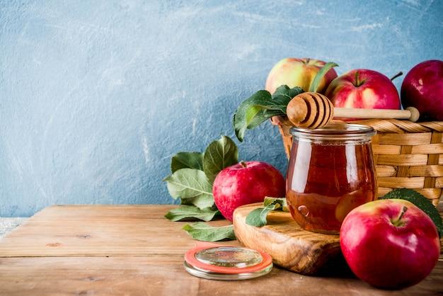 Fiesta judía rosh hashaná o concepto de fiesta de manzana, con manzanas rojas, hojas de manzana y miel en frasco, fondo de madera y azul claro
